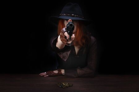 wild west girl with revolver gun sitting at the table with ammunition and silver coins on black background Stock Photo
