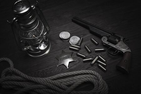Old western cold blast lantern, marshals badge and revolver with cartridges on wooden table Stock Photo