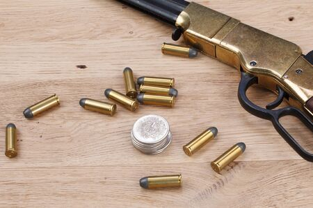 Wild west gun with rounds on wooden table