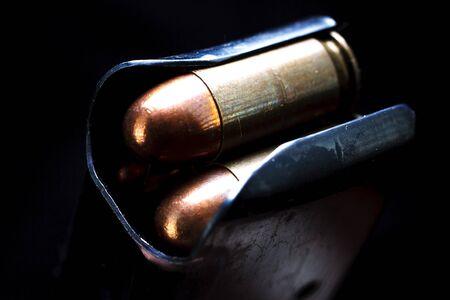 .45 caliber submachine gun cartridges in box magazine on black background
