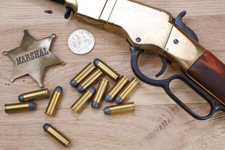 Wild west gun with ammunition and marshal badge on wooden background 版權商用圖片