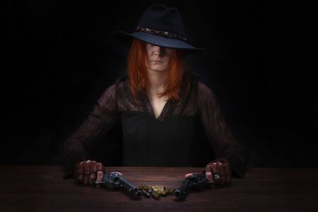 wild west girl with revolver gun sitting at the table with ammunition and silver coins on black background
