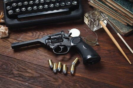 Writing a crime fiction story - old retro vintage typewriter and revolver gun with ammunitions, books, papers, old ink pen on wooden table Imagens