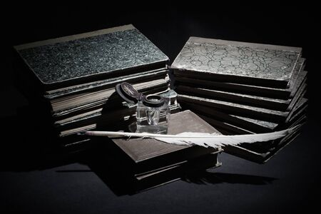 Old books, papers, ink pen and inkpot. Retro style photo in sepia tone.