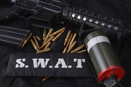 Special weapons and tactics team weapon, ammunitions and equipment on black uniform background Reklamní fotografie