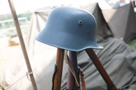 Rifles pyramids with ammunition and german steel helmet, First World War-era reenactment