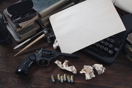 Writing a crime fiction story - old retro vintage typewriter and revolver gun with ammunitions, books, blank paper, old ink pen on wooden table