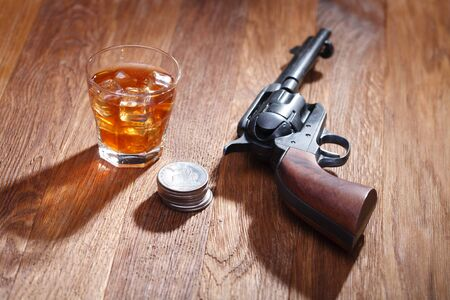 Wild west revolver with glass of whisky and ice with old silver dollar on wooden bar table Stockfoto