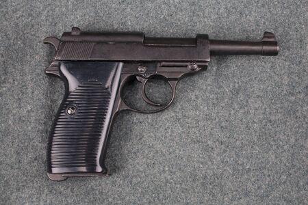 WWII era nazi german army 9 mm semi-automatic pistol on camouflaged uniform background