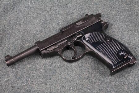 WWII era german army 9 mm semi-automatic pistol on camouflaged uniform background