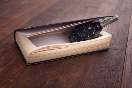 black hand grenade hidden in a book