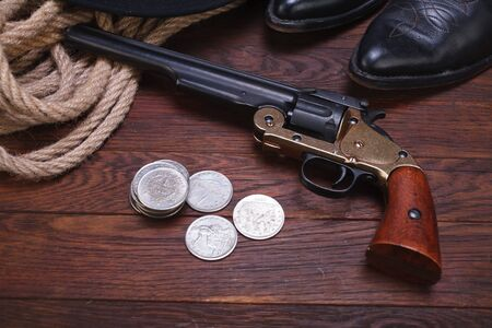 Old western gun with silver dollars with hat, rope and boots