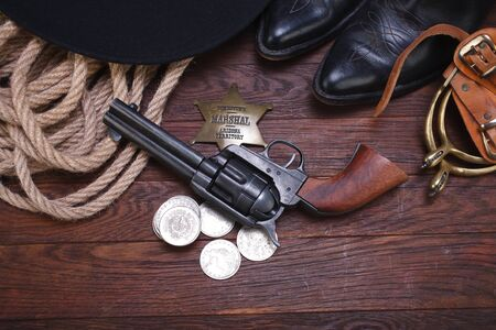 Old western gun with marshal badge and silver dollars with hat, rope and boots