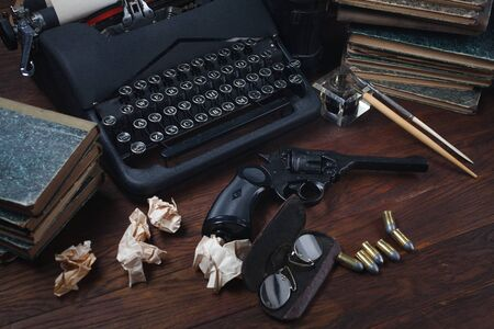 Writing a crime fiction book - old retro vintage typewriter and revolver gun with ammunitions, books, papers, old ink pen on wooden table
