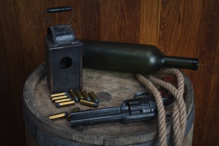 Old western revolver with cartridges on wooden barrel
