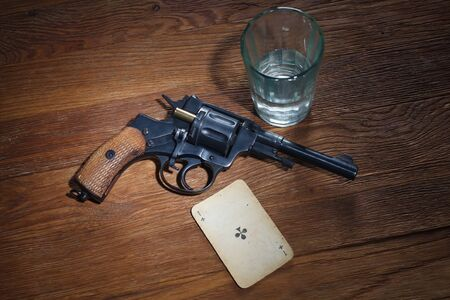 russian roulette - Ace of Clubs plaing card, glass of vodka and revolver with one cartridge in drum on wooden table background Imagens