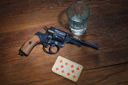 russian roulette - Ten of Diamonds plaing card, glass of vodka and revolver with one cartridge in drum on wooden table background