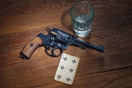 russian roulette - Six of Clubs plaing card, glass of vodka and revolver with one cartridge in drum on wooden table background Imagens