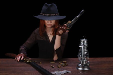 wild west girl with revolver gun sitting at the table with ammunition and silver coins on black background Imagens