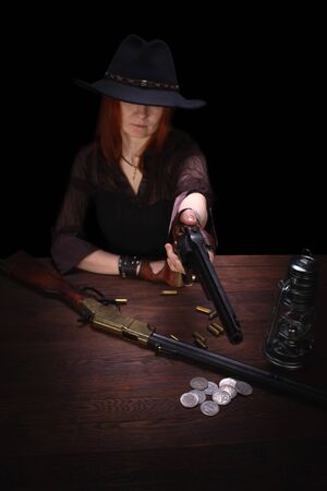 wild west girl shooting from revolver gun at the table with ammunition and silver coins on black background Stock Photo