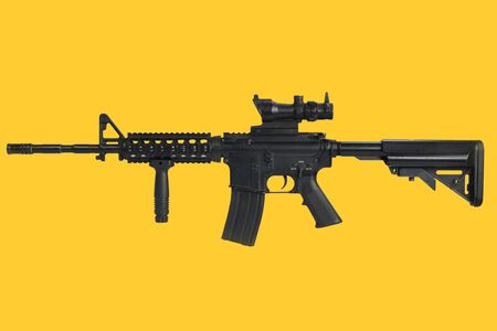 Carbine with optic sight and a foregrip on yellow background