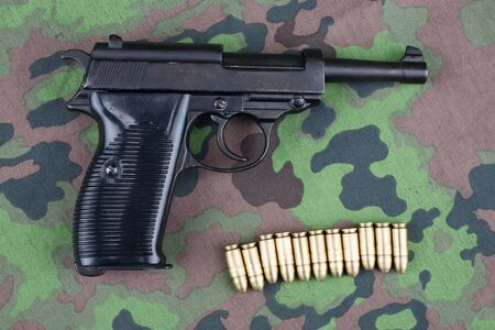 WWII era german army 9 mm semi-automatic pistol with ammunition on camouflaged uniform background