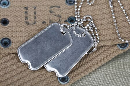 A pair of blank dog tags on U.S. Army uniform world war two era background