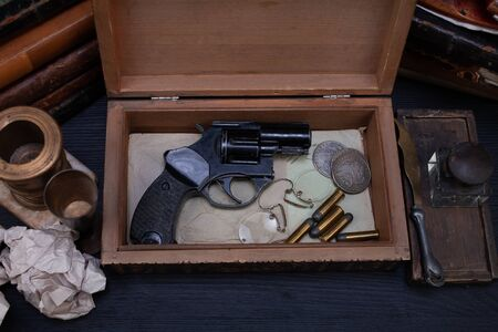 Memorabilia - old retro vintage revolver gun with ammunitions in wooden box for letters