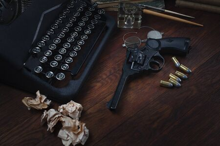 Crime fiction story - old retro vintage typewriter and revolver gun with ammunitions, books, blank paper, old ink pen on wooden table Zdjęcie Seryjne