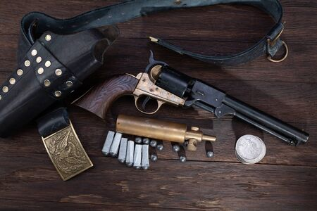 Firearms of the Old West - Percussion Army Revolver with paper cartridges, bullets, powder flask and holster on wooden table