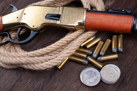 Wild west gun - lever-action repeating rifle with ammunition and silver dollar coins on wooden table
