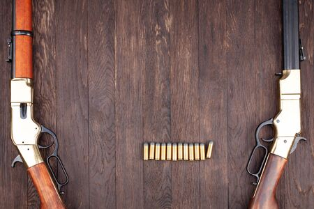 Wild west guns - lever-action repeating rifles with ammunition on wooden table