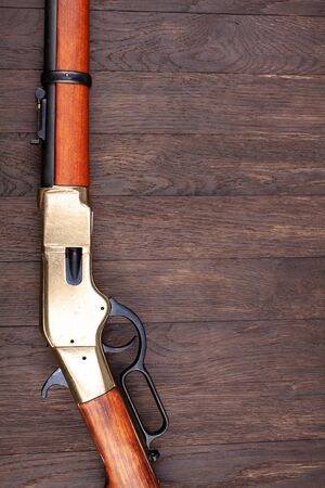 Wild west gun - lever-action repeating rifle on wooden table