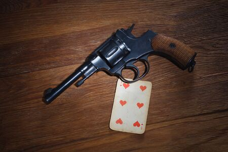 russian roulette - Six of Hearts plaing card and revolver with one cartridge in drum on wooden table background