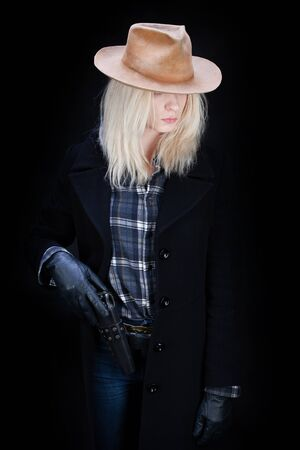 wild west blonde girl with revolver on black background Stock Photo