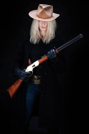 wild west blonde girl with rifle on black background Stock Photo