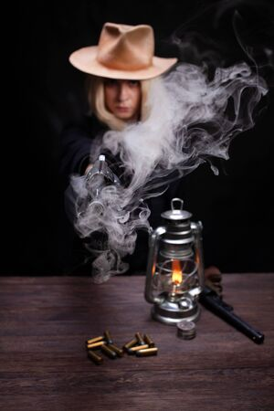 wild west blonde girl shooting from revolver gun at the table with ammunition and silver coins on black background Stock Photo