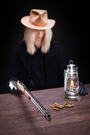 wild west blonde girl shooting from revolver gun at the table with ammunition and silver coins on black background