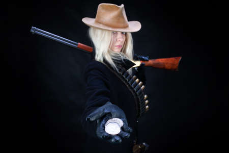 wild west blonde girl with silver dollars in hand and gun on black background