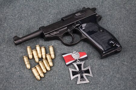 semi-automatic pistol with Iron Cross award on army grey uniform background