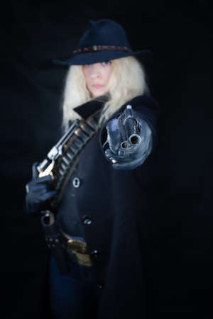 wild west blonde girl wearing black hat shooting from revolver on black background Stock Photo