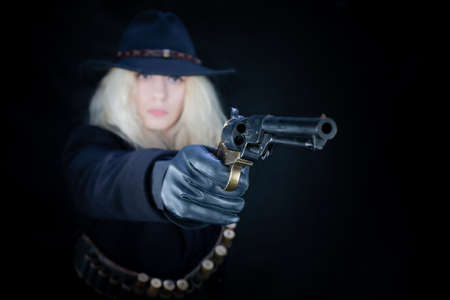wild west blonde girl wearing black hat shooting from revolver on black background