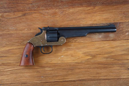 old west era .44 smith and wesson single action revolver isolated on wooden background