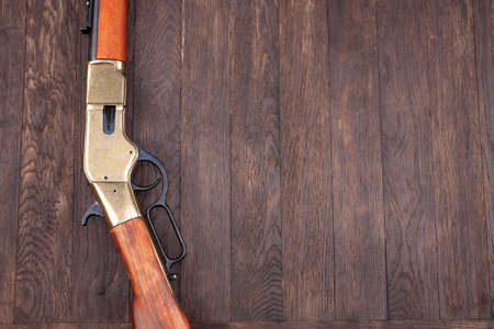 Old west gun - lever-action repeating rifles with ammunition on wooden table