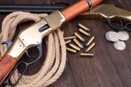 Old west gun - lever-action repeating rifle with ammunition and silver dollar coins on wooden table