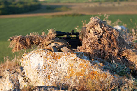 sniper in ghillie (camouflage) suit with a high-precision rifle with optic scope in a combat position in the mountains