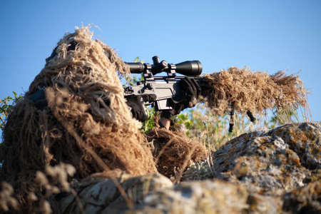 sniper in ghillie (camouflage) suit with a high-precision rifle with optic scope in a combat position in the mountains Banque d'images