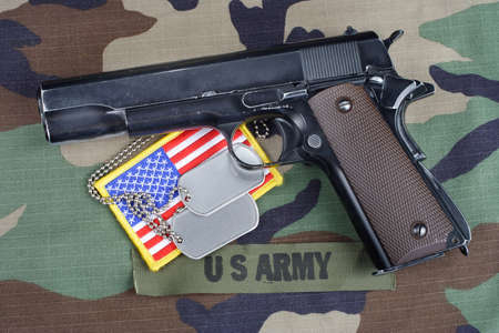 US ARMY branch tape, M1911 handgun with dog tags on woodland camouflage uniform