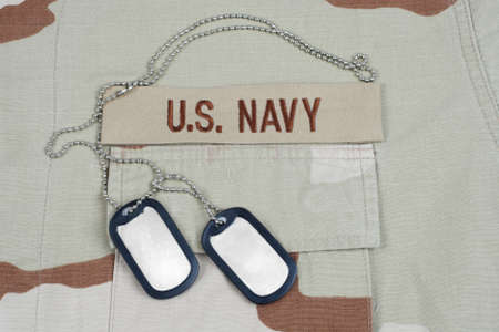 US NAVY branch tape with dog tags on desert camouflage uniform background