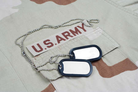 US ARMY branch tape with dog tags on desert camouflage uniform background